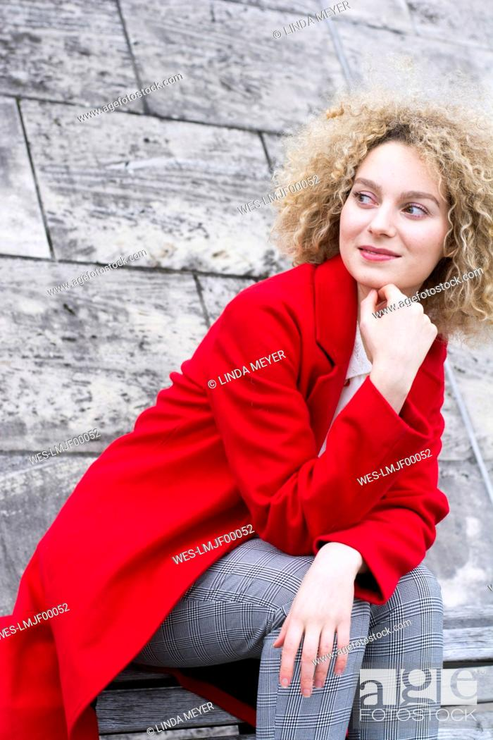 Stock Photo: Portrait of smiling blond woman with ringlets wearing red coat watching something.