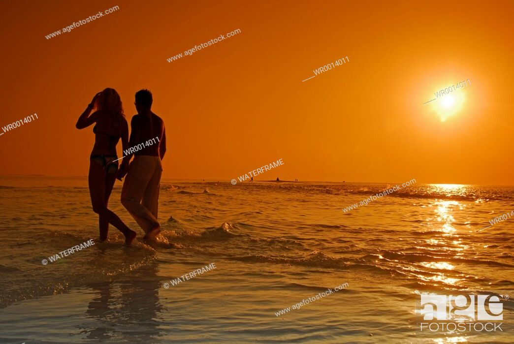 Stock Photo: Couple at Sunset, Indian Ocean, Maldives.
