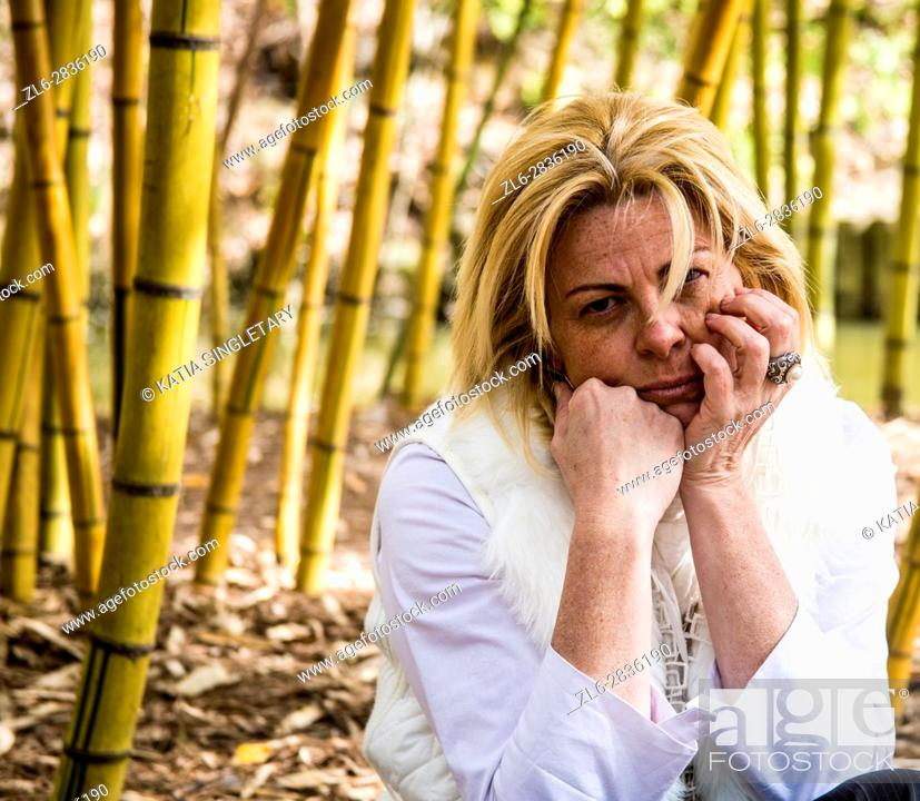 Stock Photo: Melancholic blond woman sitting in the middle of bamboos. She is dressed in white, has sunglasses on and looks sad, depressed.