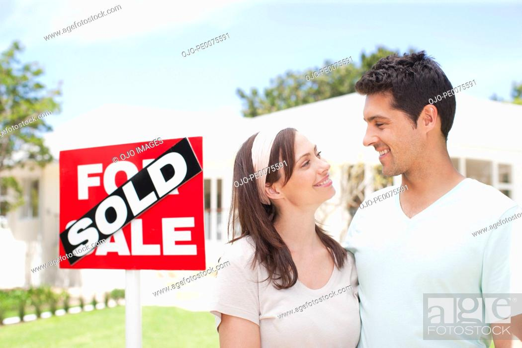 Stock Photo: Couple standing near sold sign of their new house.