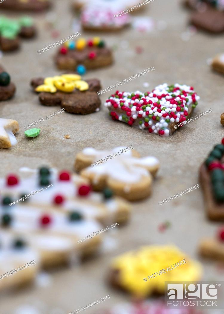 Stock Photo: 10 December 2020, Saxony-Anhalt, Magdeburg: A heart with colourful sugar balls lies on a tray next to other Christmas cookies.