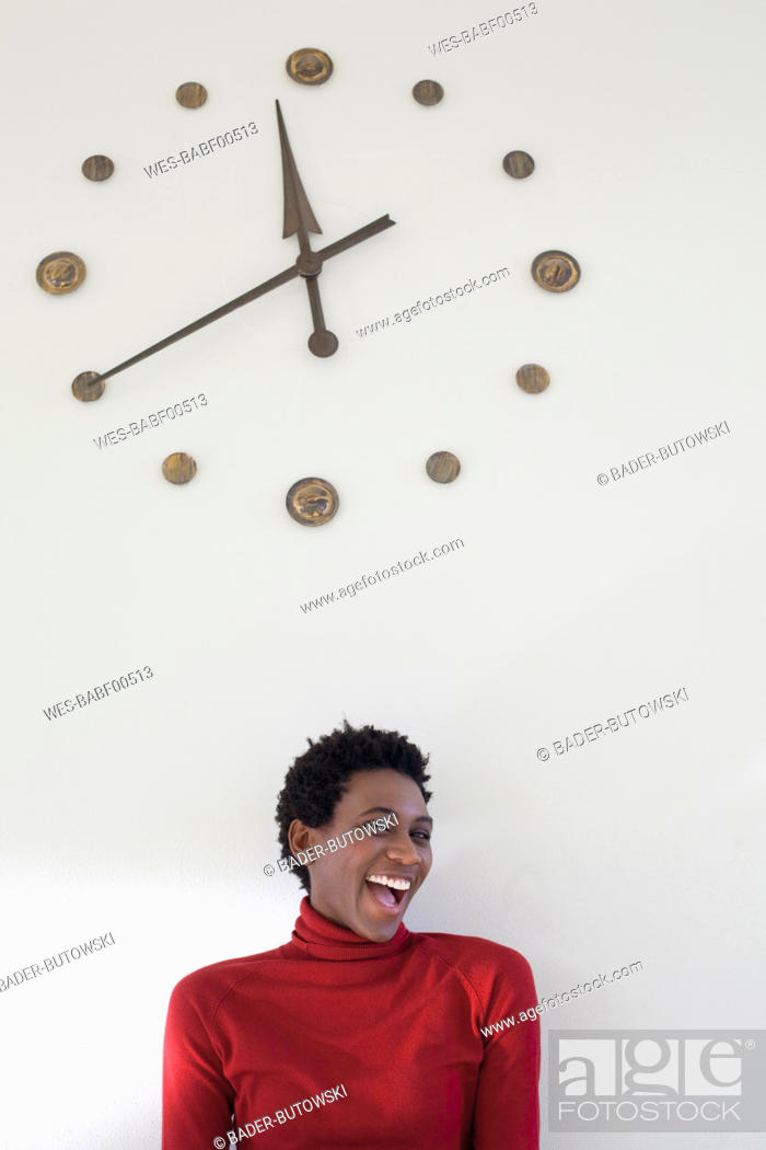 Stock Photo: Germany, Leipzig, University student laughing with wall clock in background.