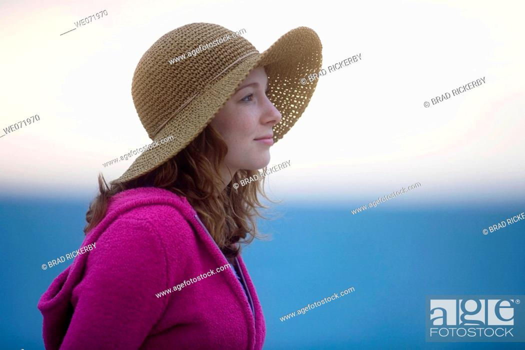 Stock Photo: 20 year old woman gazes reflectively at beach dusk over the Pacific ocean in Los Angeles, California, USA.