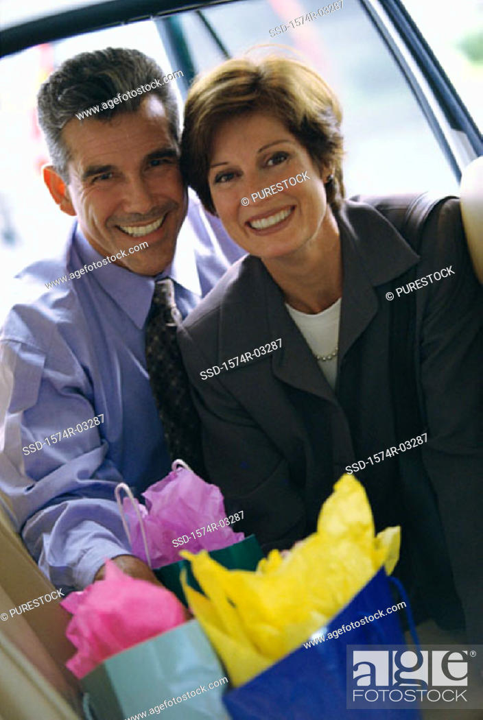 Stock Photo: Portrait of a mature couple with shopping bags.
