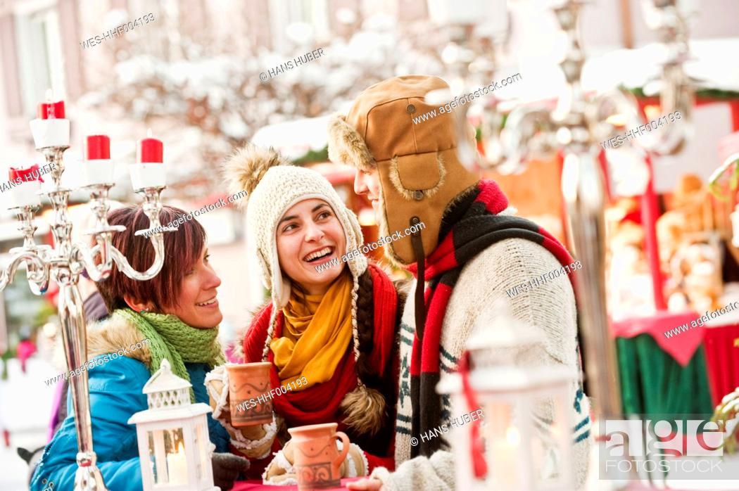 Stock Photo: Austria, Salzburg, Man and women at christmas market, smiling.