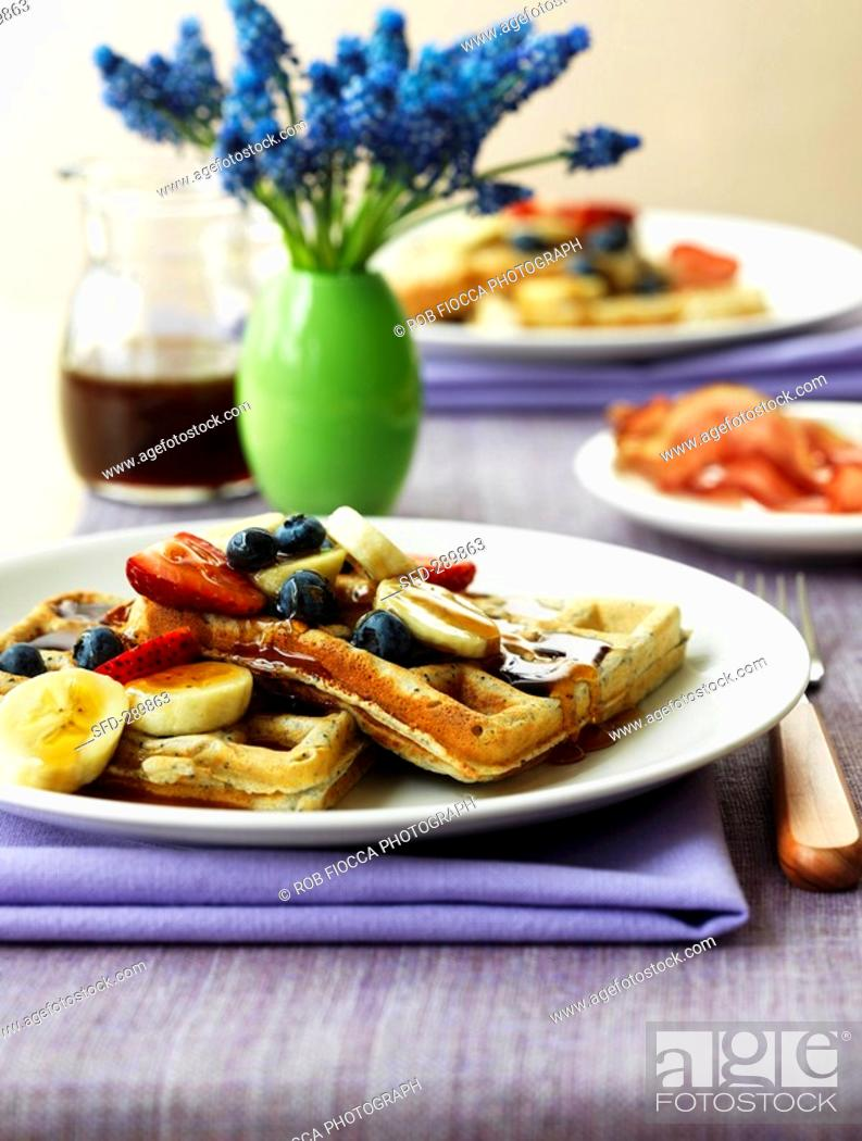 Stock Photo: Wholemeal waffles with bananas, berries and maple syrup.