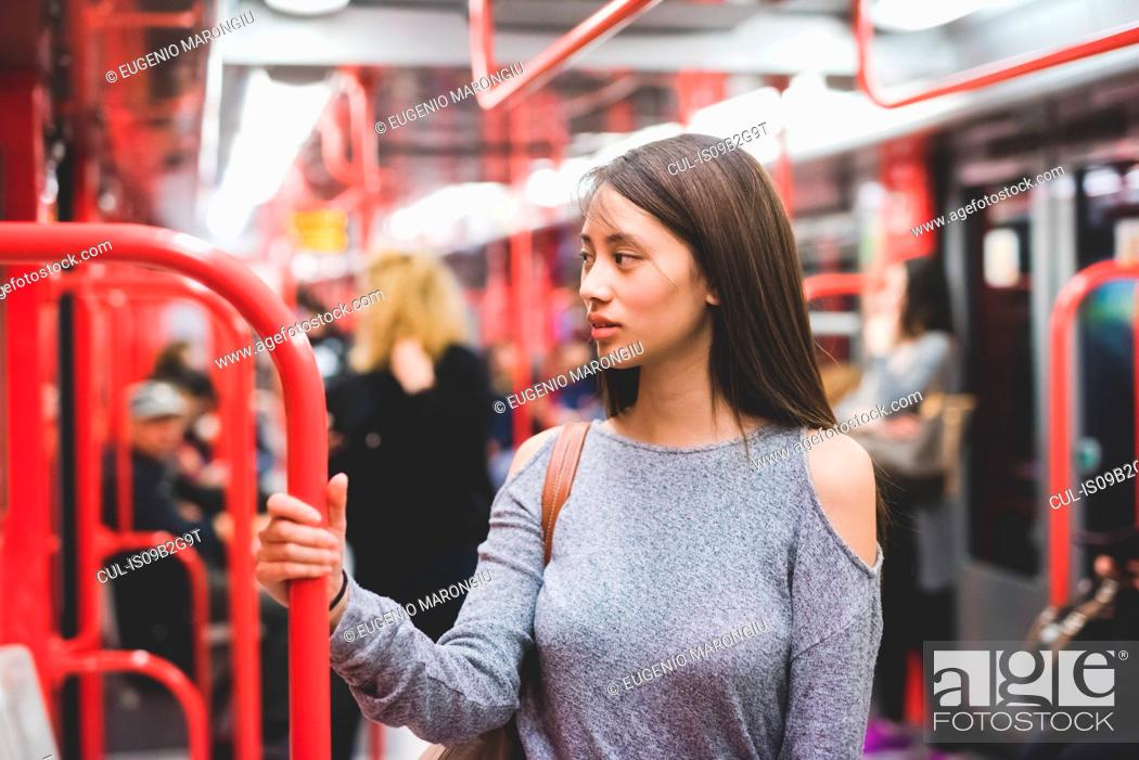 Stock Photo: Young woman traveling on train carriage looking over her shoulder.