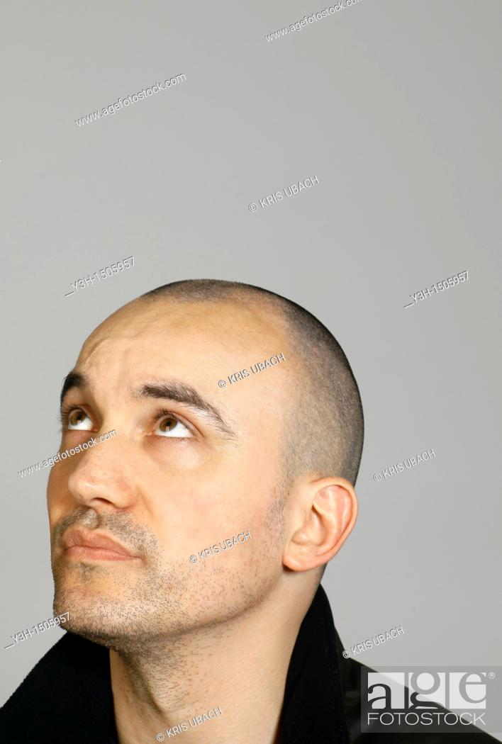 Stock Photo: Studio shot of man with shaved head, looking upwards.