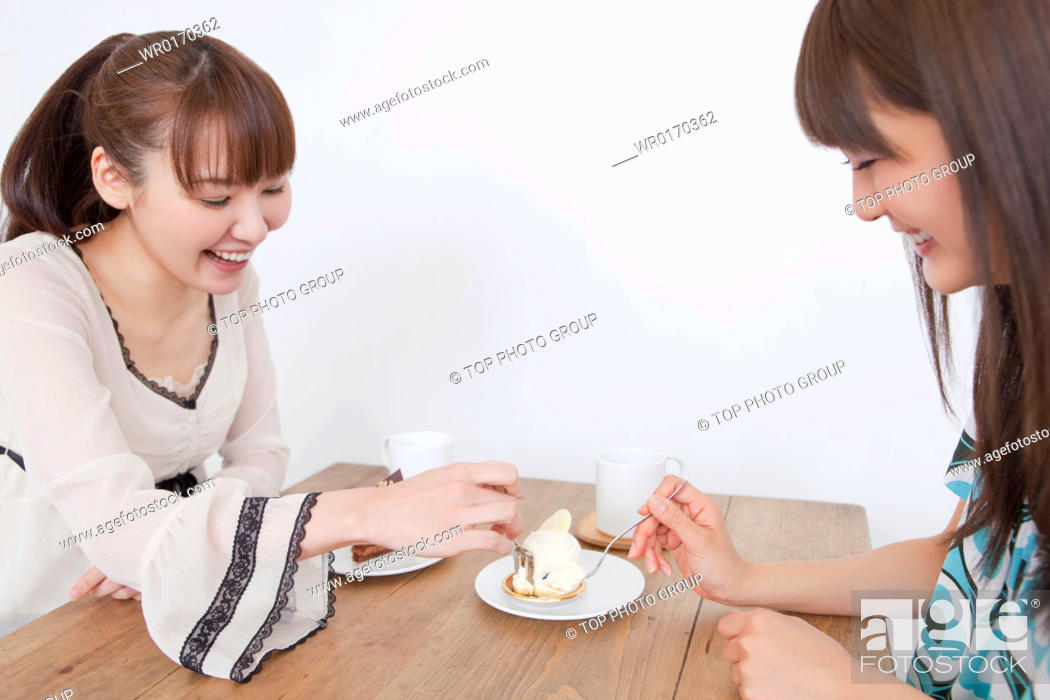 Stock Photo: Young women eating cake.