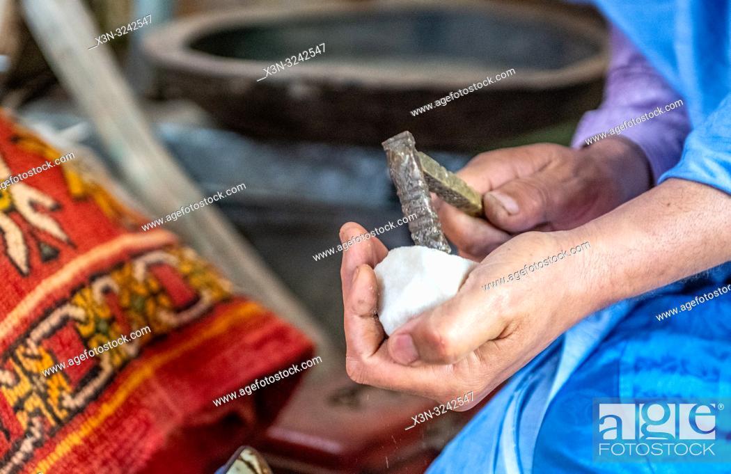 Photo de stock: Berber man uses crude hammer to break off piece of sugar for traditional Moroccan tea ceremony, Tighmert Oasis, Morocco.