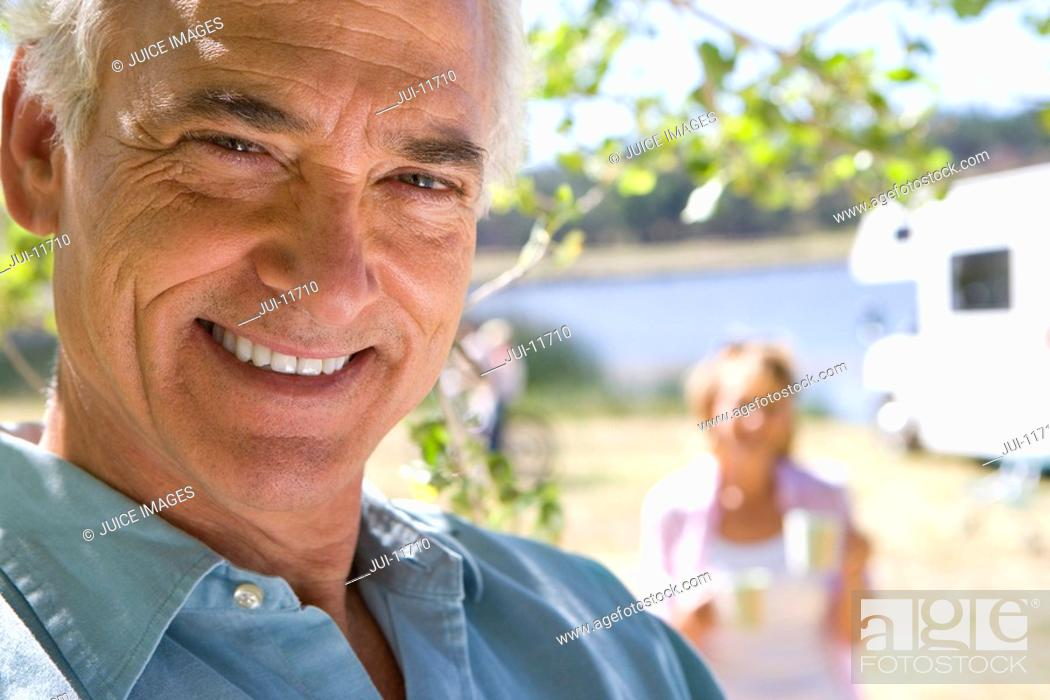 Stock Photo: Mature man by wife and motor home outdoors, smiling, portrait, close-up.