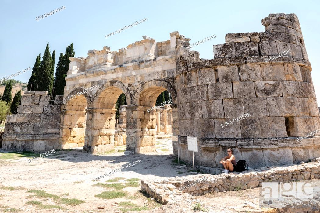 Stock Photo: Woman sits near Byzantine Gate at Hierapolis ancient city in Pamukkale, Turkey. 25 August 2017.