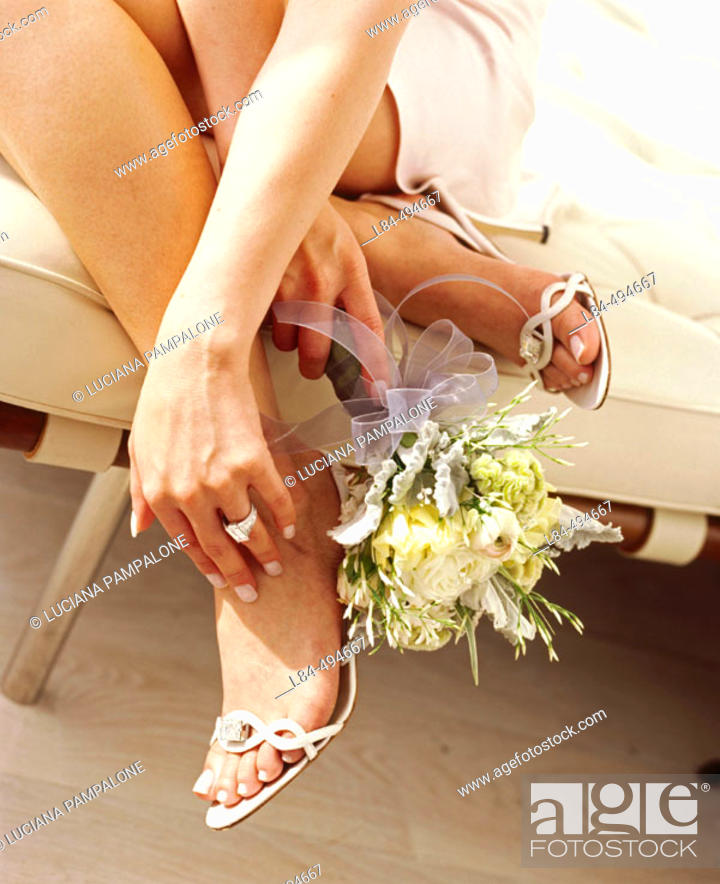 Stock Photo: woman holding bouquet by feet.