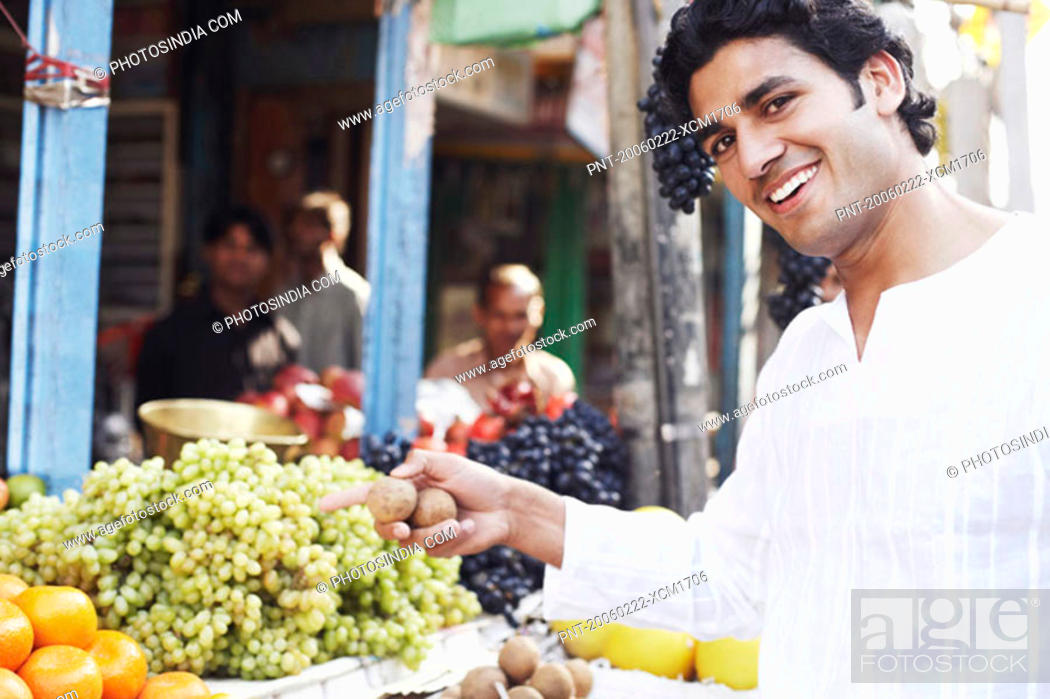 Stock Photo: Portrait of a young man standing at a fruit stand.