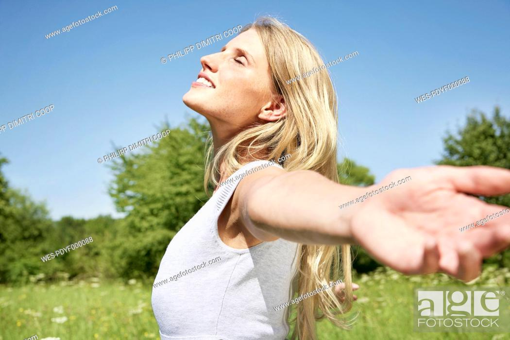 Stock Photo: Germany, Cologne, Young woman stretching in meadow.