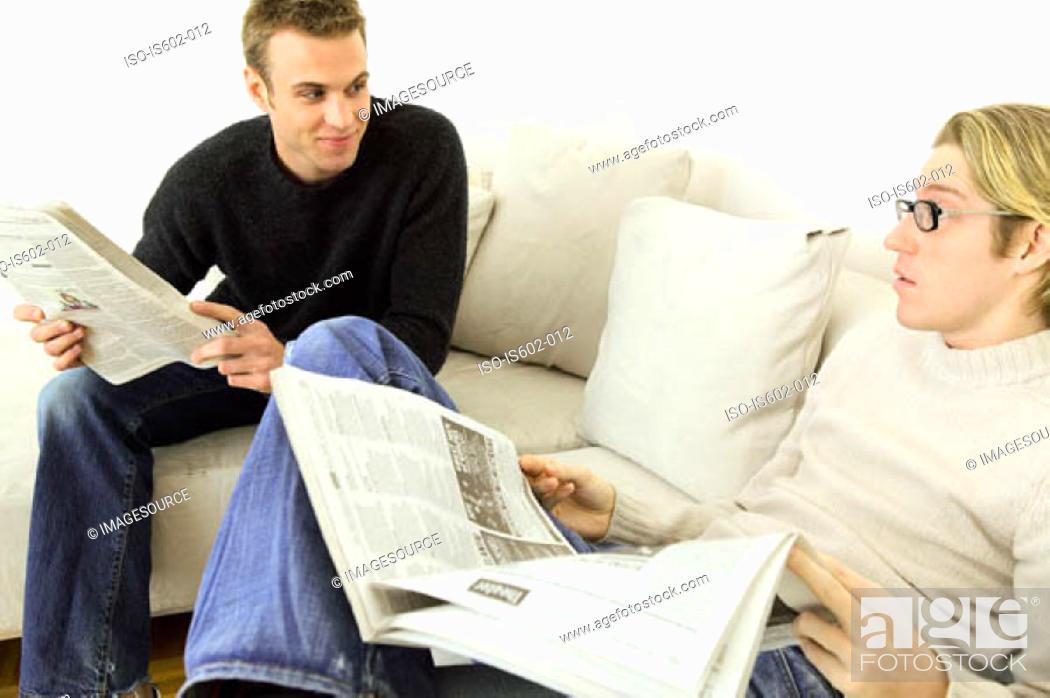 Stock Photo: Men reading newspapers on sofa.