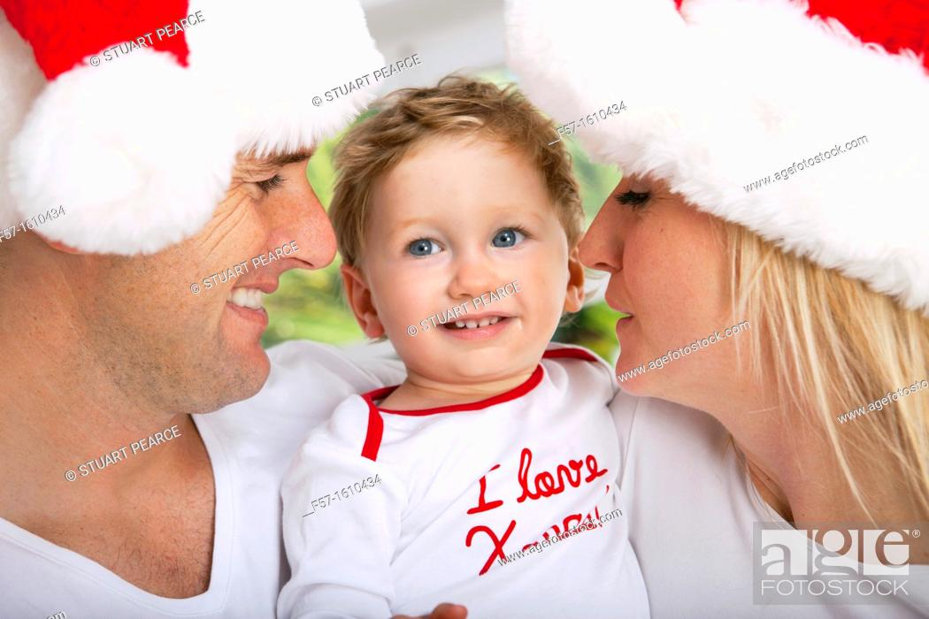 Stock Photo: Parents with their one year old son at Christmas time.