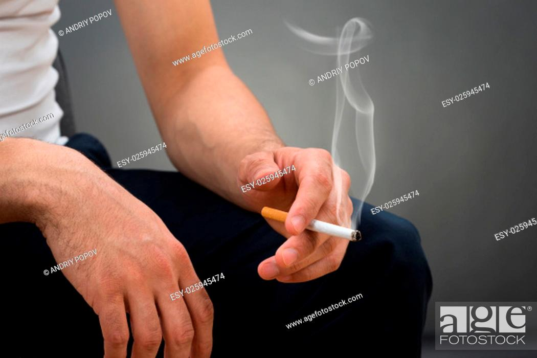 Stock Photo: Midsection of man holding cigarette while sitting against gray background.