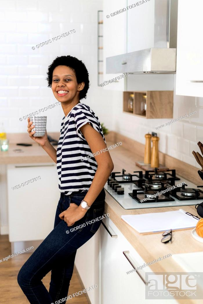 Stock Photo: Portrait of smiling young woman holding mug in kitchen at home.