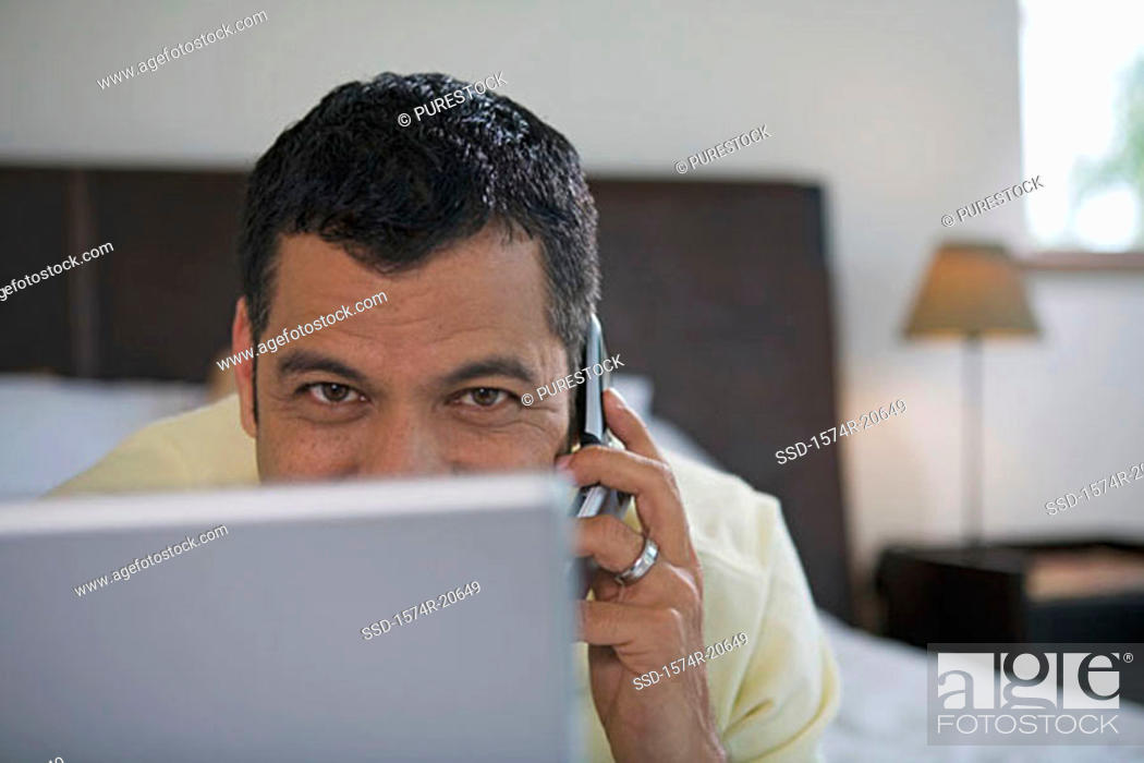 Stock Photo: Portrait of a mature man lying in front of a laptop and talking on a mobile phone.