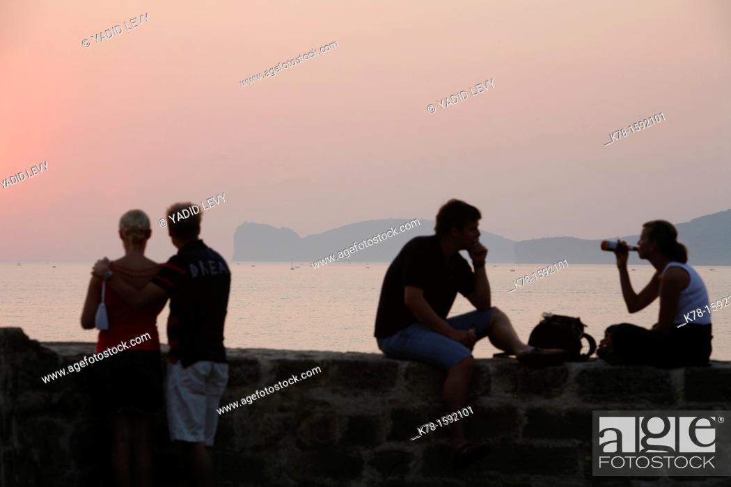 Stock Photo: Couple sitting on the city walls looking over the Capo Caccia, Alghero, Sardinia, Italy.