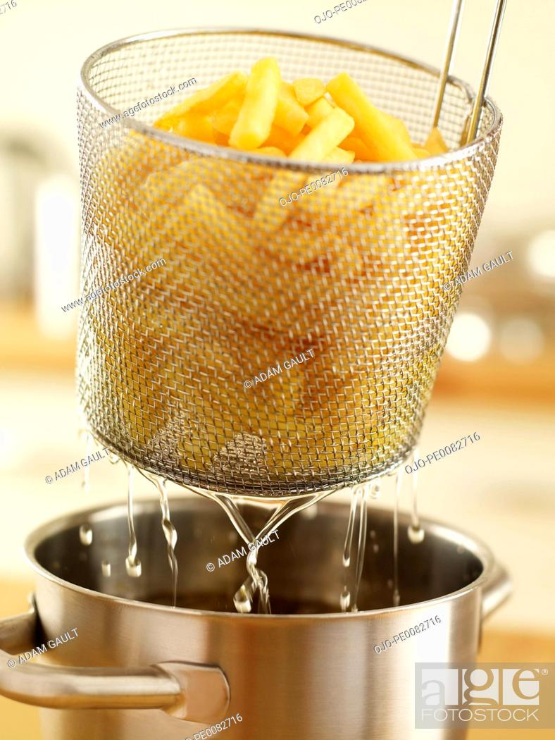 Stock Photo: Basket of french fries being removed from deep fryer.