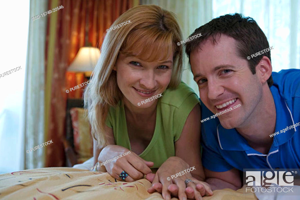 Stock Photo: Portrait of a young couple lying on the bed and smiling.