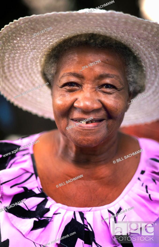 Stock Photo: Colorful local woman in hat smiling portrait in the beautiful village of La Digue in the Seychelles Islands off of Africa.
