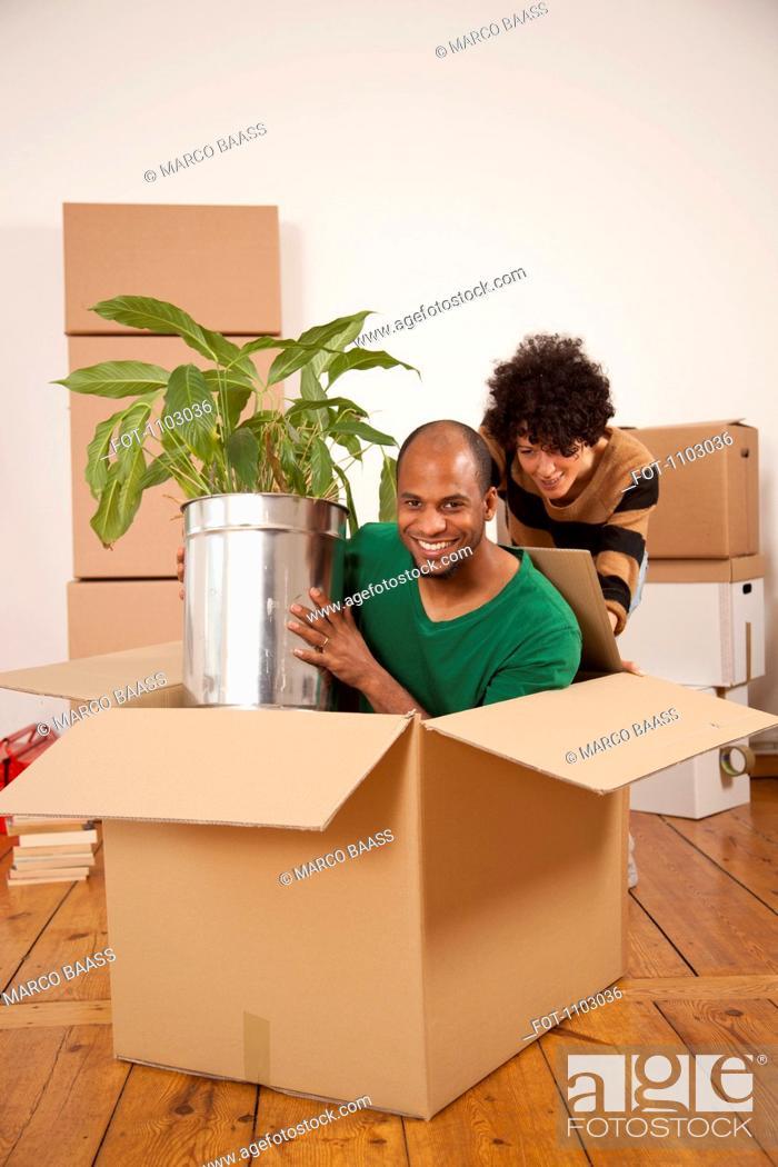 Stock Photo: A woman pushing a man sitting inside of a moving box.