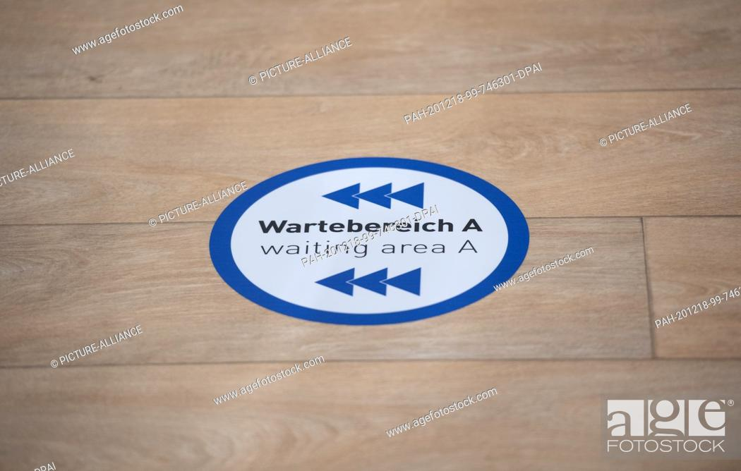 """Stock Photo: 18 December 2020, Hamburg: A sticker with the bilingual inscription """"""""Wartebereich A - waiting aerea A"""""""" is stuck on the floor in the vaccination centre."""