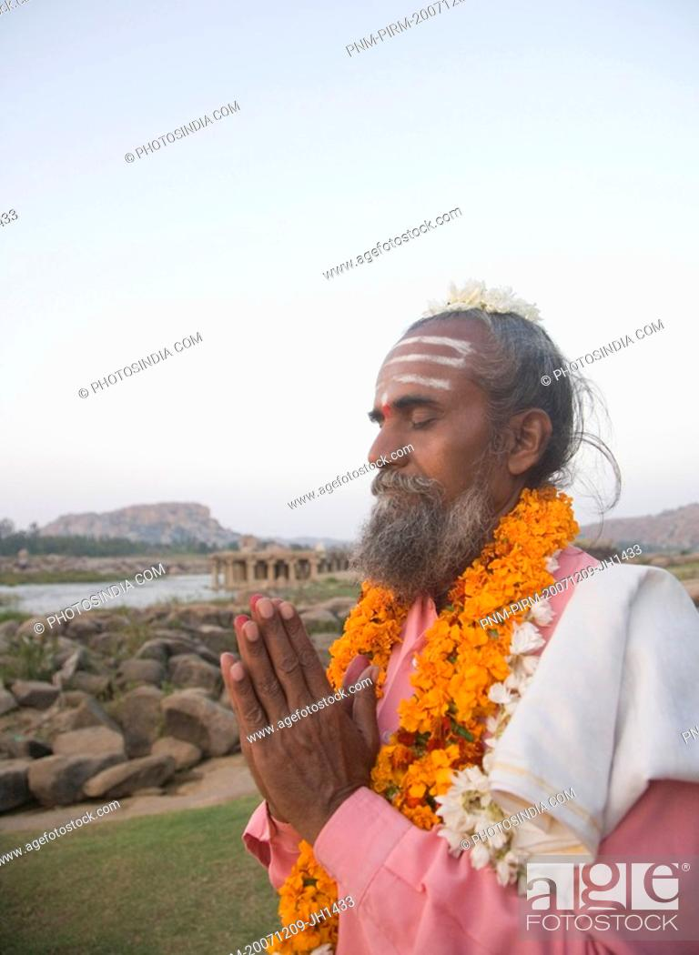 Stock Photo: Sadhu standing in a prayer position, Hampi, Karnataka, India.