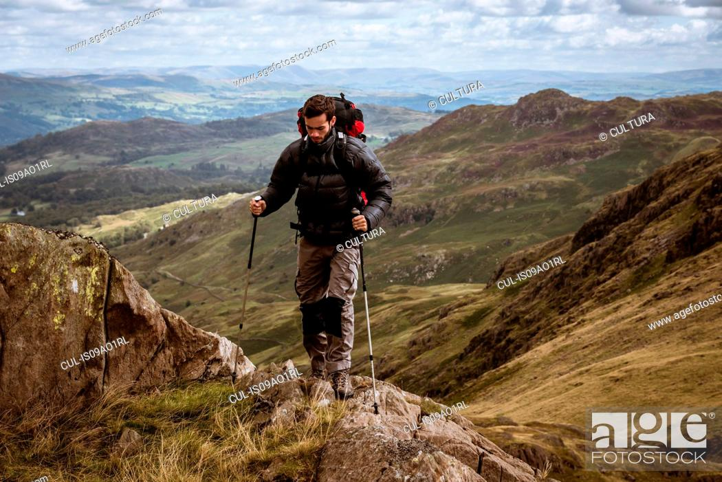 Stock Photo: Young male hiker moving up mountain, The Lake District, Cumbria, UK.