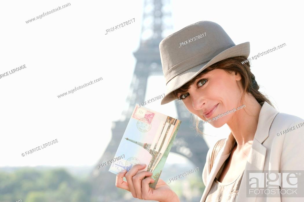 Stock Photo: Woman showing a postcard with the Eiffel Tower in the background, Paris, Ile-de-France, France.