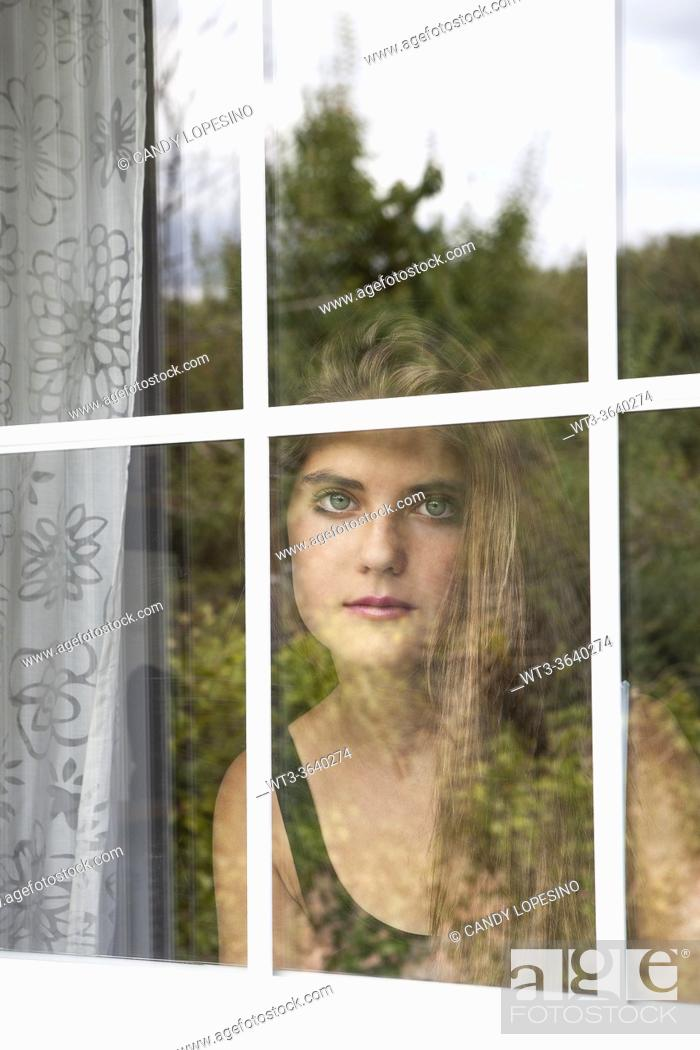 Imagen: Portrait of teenage girl behind the window, reflections of vegetation in the glass.