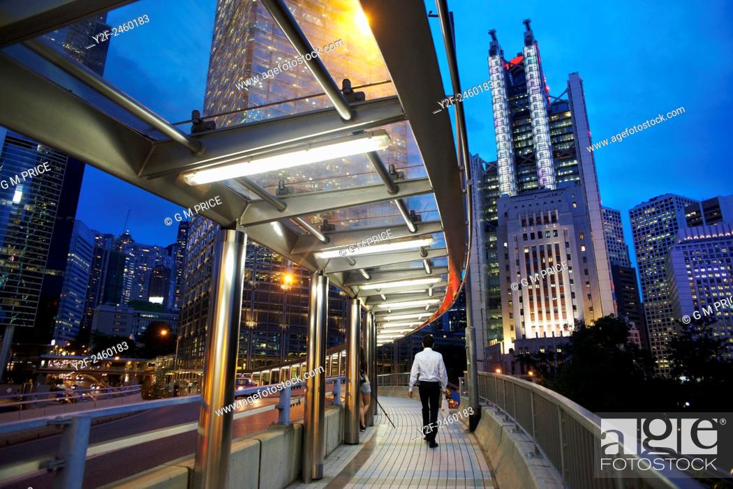 Stock Photo: man on pedestrian walkway with Hong Kong Admiralty district skyline at dusk.