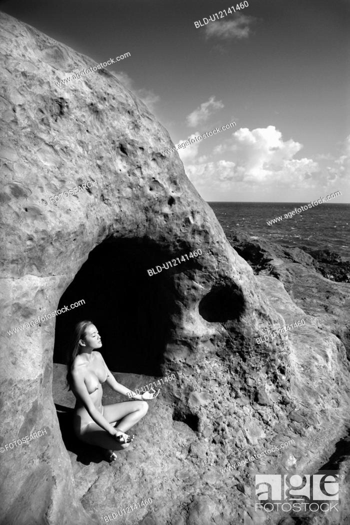 Stock Photo: Young nude woman meditating in cave with coastline.