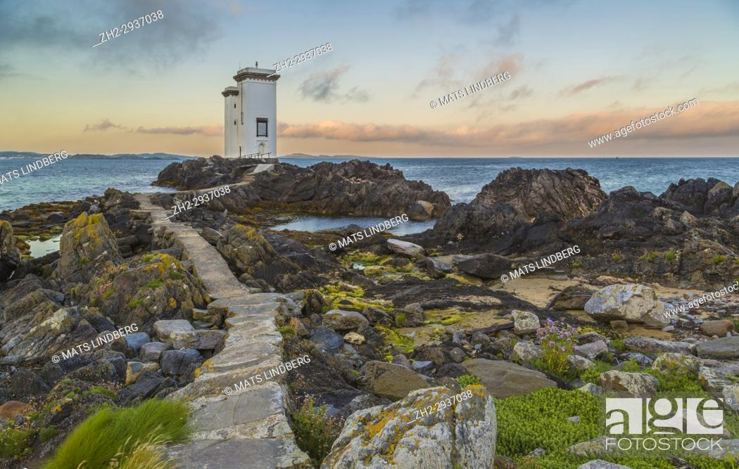 Stock Photo: Port Ellen Lighthouse, Carraig Fhada Lighthouse in evening light after sunset with nice colors on the skye with cliffs and seaweed in foreground, Port Ellen.