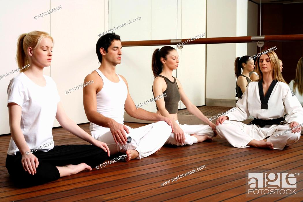 Stock Photo: Participants in a fitness class meditating.
