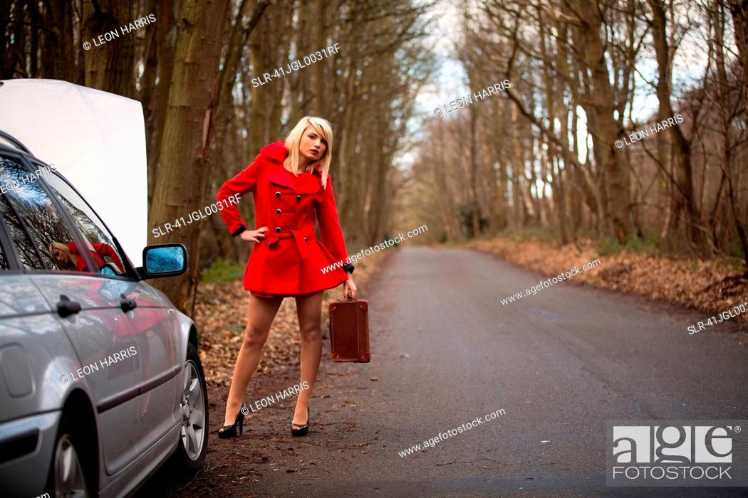 Stock Photo: Woman with broken down car in woods.