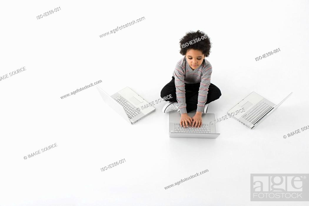 Stock Photo: Boy with three laptops.
