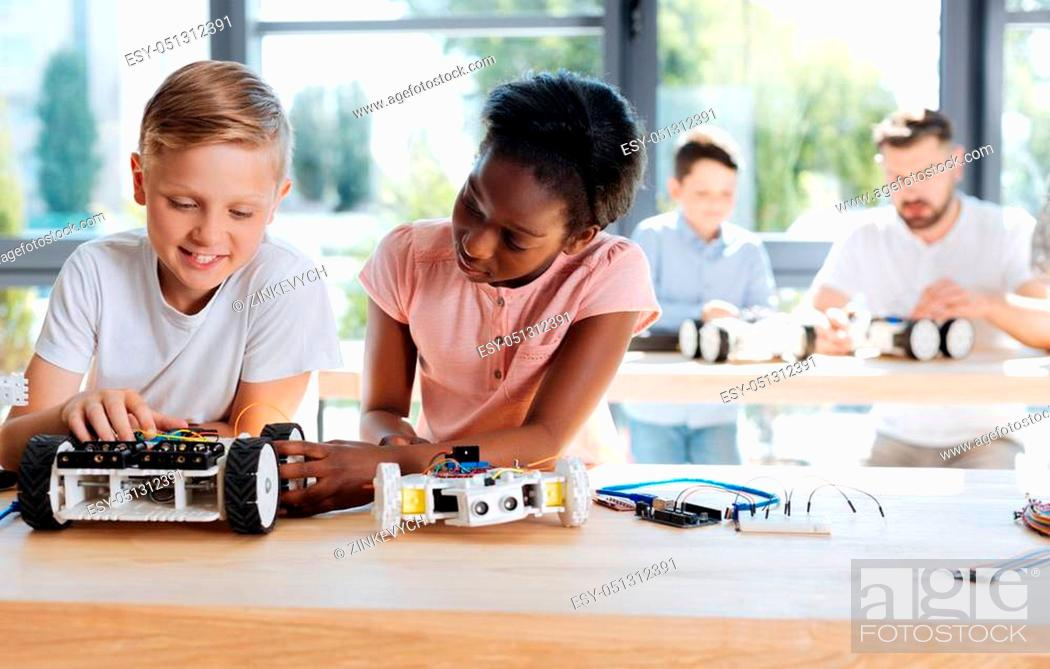 Stock Photo: Piece of advice. Pretty pre-teen girl inspecting her friends robotic vehicle while her teacher helping another student during the workshop in the background.