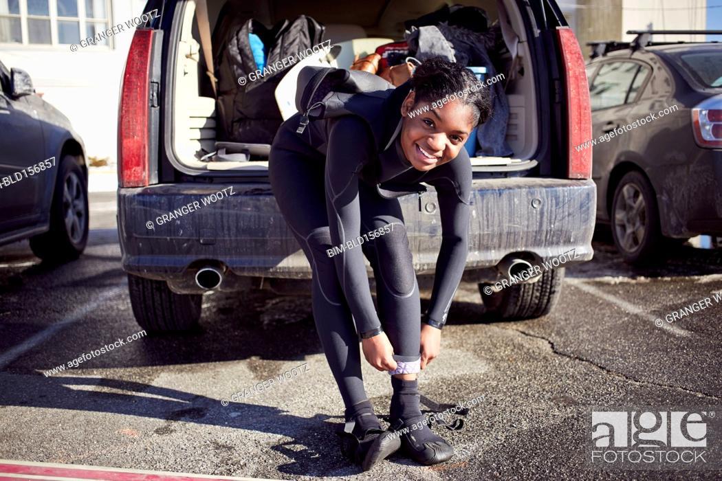 Stock Photo: Black teenage girl putting on wetsuit.