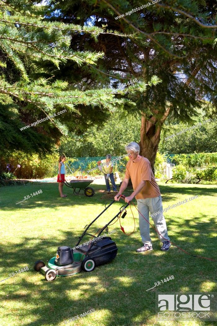 Stock Photo: Senior man mowing lawn, wife and granddaughter with wheelbarrow in background.