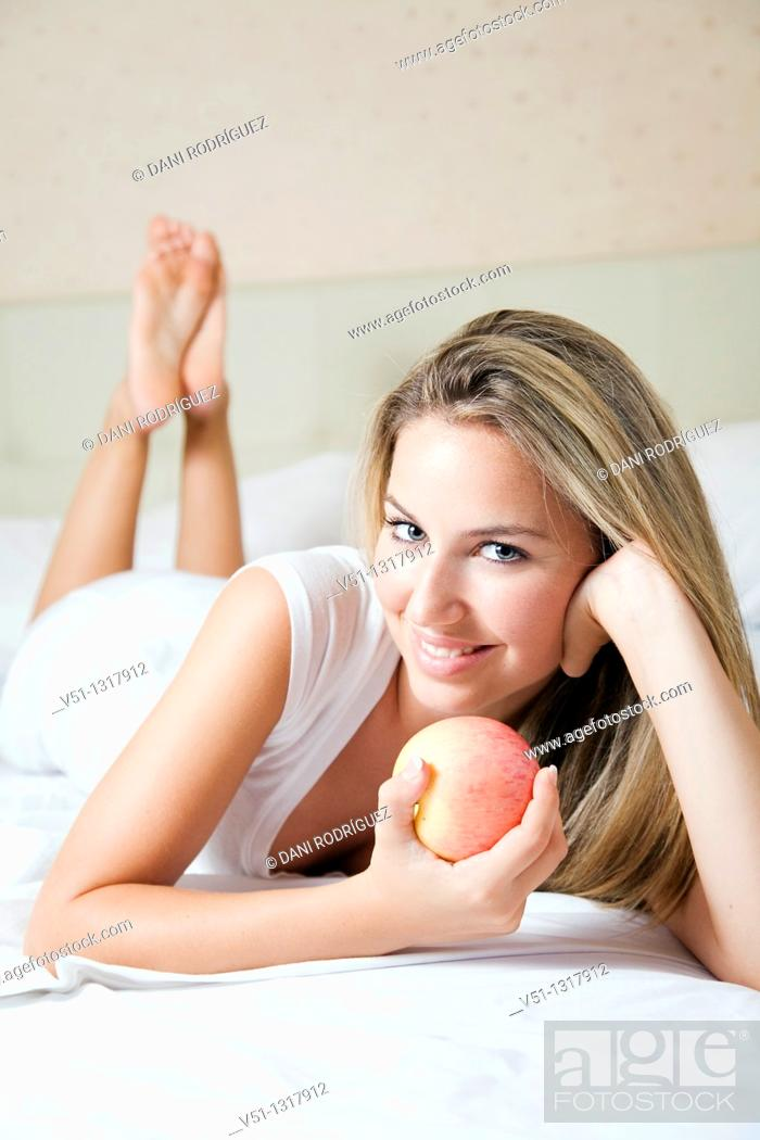 Stock Photo: Portrait of a blonde woman with apple in bed.