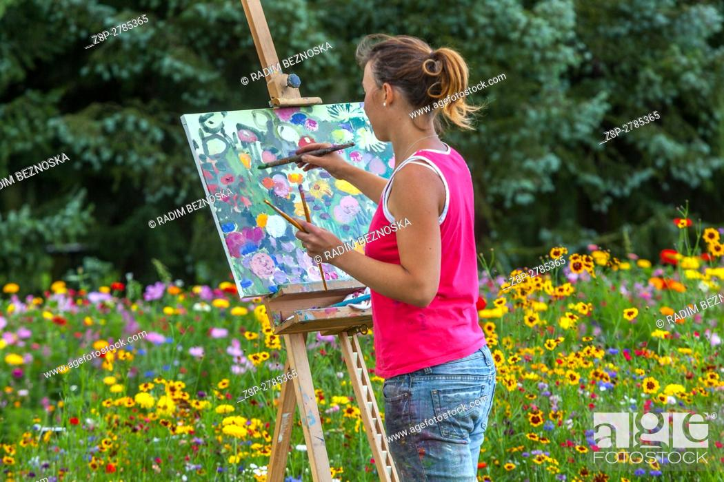 Stock Photo: The woman painter with her stand in the open air painting blossomed flower beds.