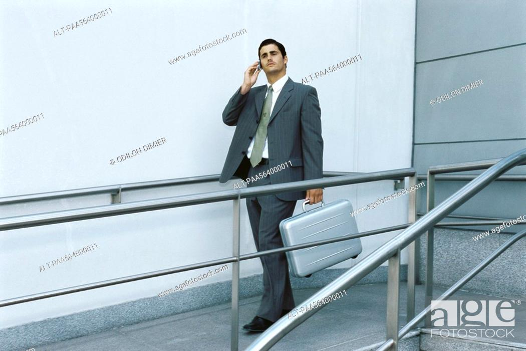 Stock Photo: Businessman walking on sidewalk using cell phone, carrying briefcase.