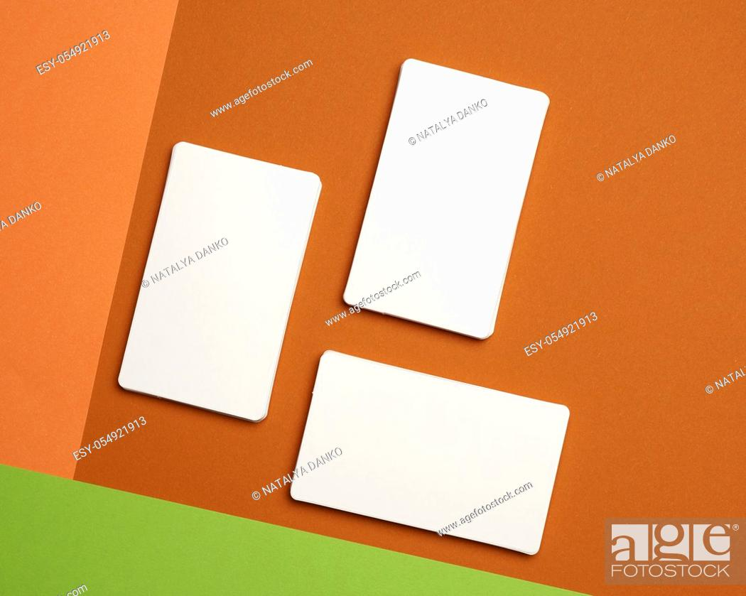 Stock Photo: piles of white paper blank business cards on orange-green background, flat lay.
