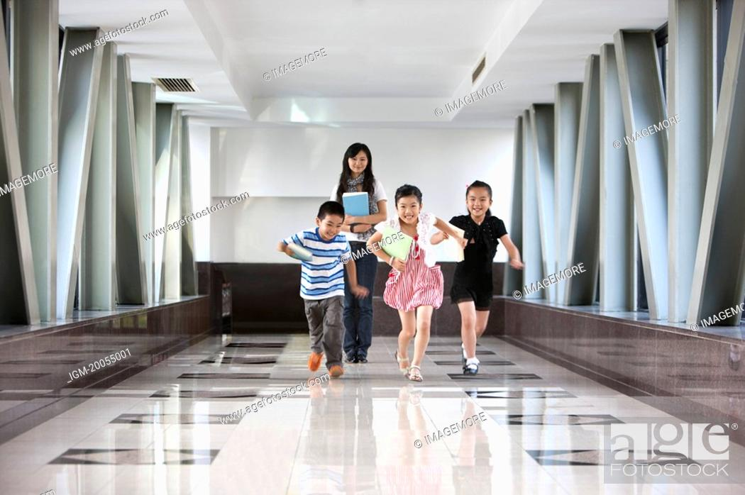 Stock Photo: Child, Four children running on the corridor with their teacher.