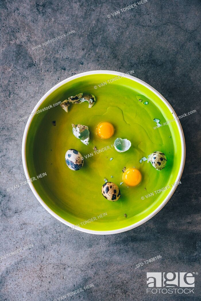 Stock Photo: Whole and cracked quail eggs in a green bowl.