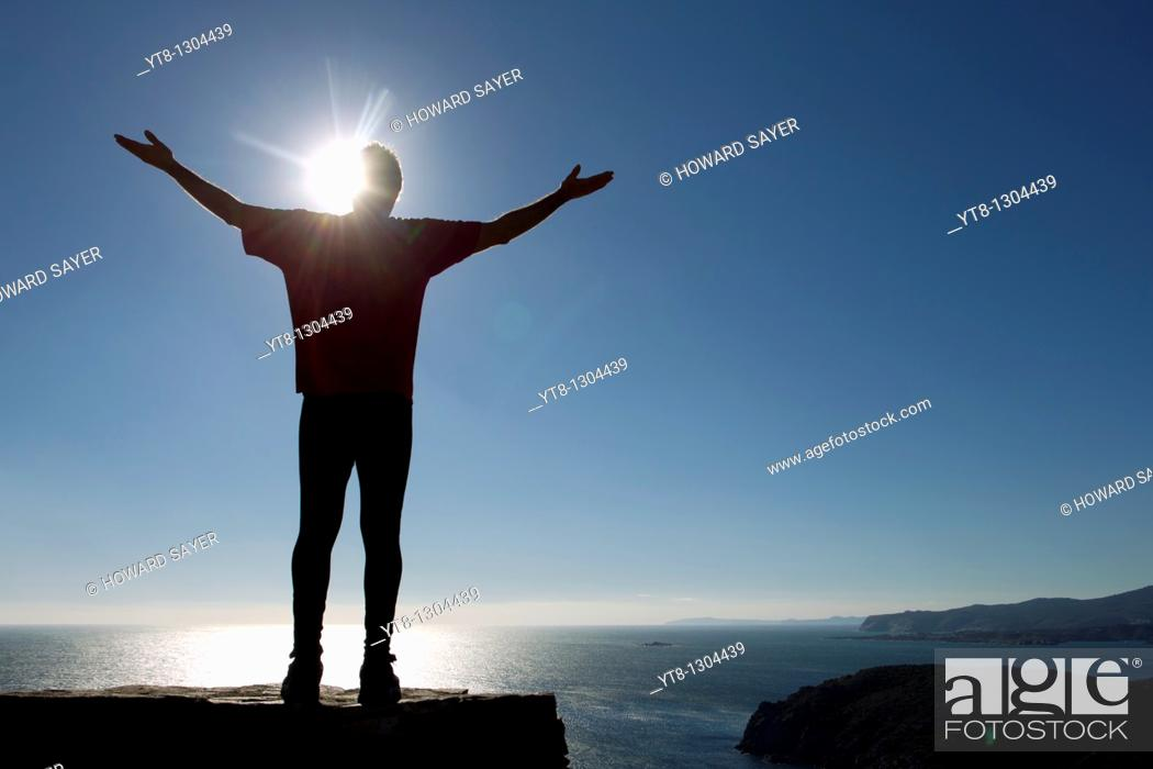 Stock Photo: Silhouette of a male athlete by the sea reaching up to the sky.